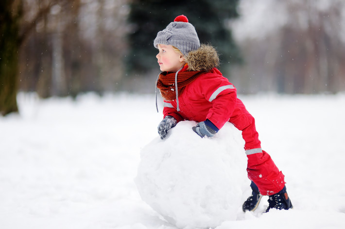 23416016 Little Boy In Red Winter Clothes Having Fun With Snowman